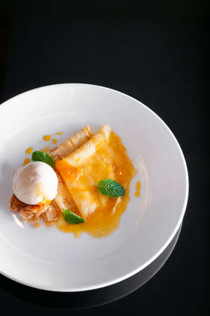 French crepe with fresh sweet orange sauce baked almond and vanilla ice cream in white plate on black table. Top view 写真素材
