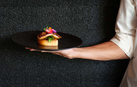 Foie Gras serving with toasted bread and green salad with black dark wall background
