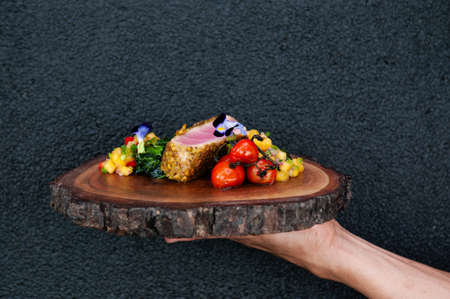 Waiter serving roasted Tuna Steaks Crusted with Herbs and grilled vegetable and mango salsa on wood plate. against black wall