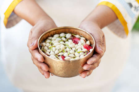 Thai greeting culture with water dipper bowl with jasmine and flowers in woman hands for Songkran day, New year or mother day. close up