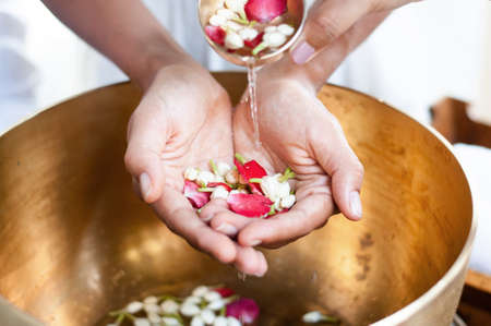 Thai culture water dipper bowl with jasmine and flowers pouring water on hands for greeting on Songkran day, New year or mother day. close up