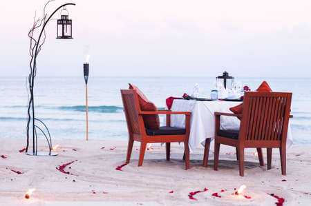 Honeymoon dinner table on island beach with candle at evening in Thailand 写真素材