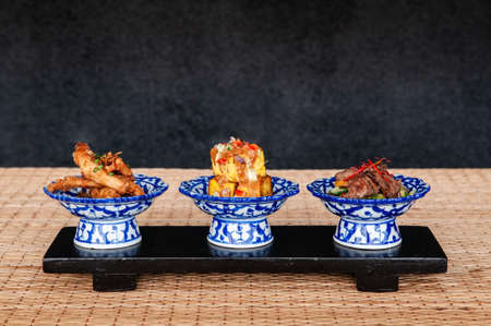 Thai fried snack fried tofu fried pork in ceramic bowls with dark background Фото со стока