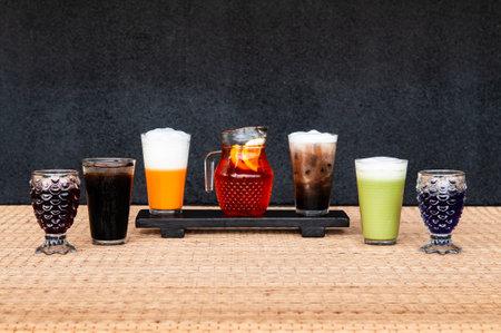 Assorted Thai soft drinks ice tea lemon thai milk tea green tea and rosella juice with dark background