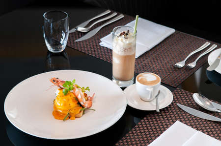 Egg Benedict with prawn and hollandaise sauce with morning drink set ice and hot coffee