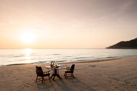 Romantic breakfast on beach. Breakfast table with island sunrise and serene seaview