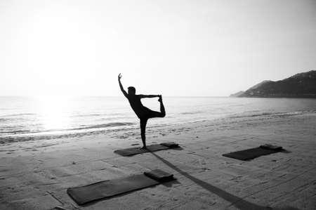 Silhouette Morning Yoga against rising sun on island beach