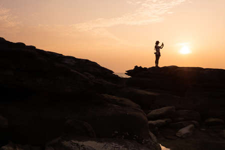 Female tourist stand on rock cape and taking sunset image on tropical island. silhouette sunset view on Koh Kood - Thailand