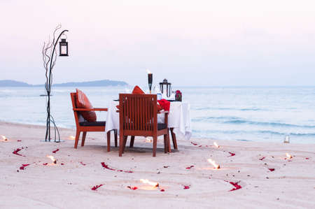 Honeymoon dinner table on island beach with candle at evening in Thailand Фото со стока