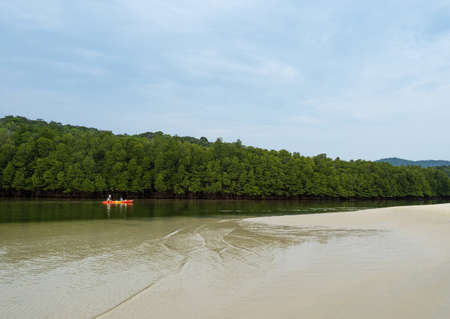 APR 9, 2021 Koh Kood - Thailand - Asian tourist on Kayak boat in mangrove forest canal on tropical island. Outdoor recreation kayaking sport. Фото со стока