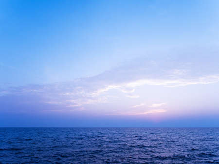 Peaceful serene sea scape and blue tone sunset or sunrise sky with clouds, tropical island ocean view at dawn or dusk