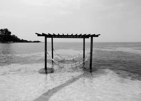 Serene peaceful sea on tropical island beach with gazebo and hammocks in summer. Koh Kood - Thailand - Black and white
