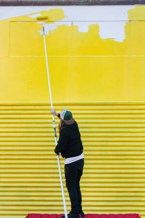 Man with paint roller, painting wall on the street yellow while standing on a red platform