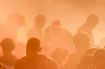 Silhouette of people dancing in colorful smoke at a festival