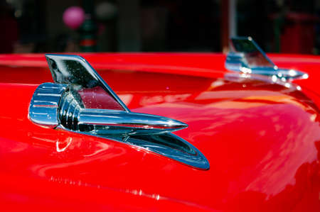 Close up view of shiny chrome metal arrow hood element