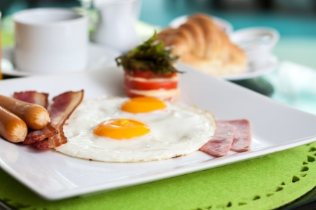 Fried Eggs with sausage, bacon, ham and tomato cheese  Breakfast  photo