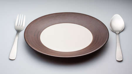 stoneware: Plates with a silver fork and spoon isolated on gray background Stock Photo