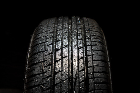 all weather: Car tires close-up on black background Stock Photo