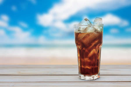 the carbonation: glass of cola with ice on wood