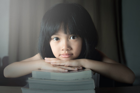 A little girl reading the book 스톡 콘텐츠