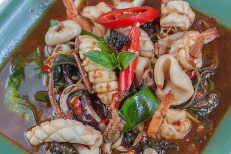cangrejo: picante de calamar y cangrejo alevines con la hierba en la comida tailandesa