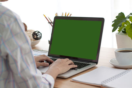 Over the shoulder shot of a woman typing on a computer laptop with a key-green screen. Woman hand typing laptop with green screen. Standard-Bild