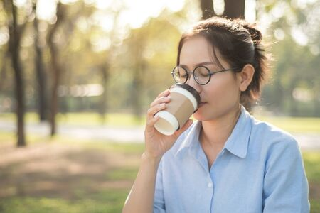 Asian woman drinking hot coffee with feeling happy in the green graden.