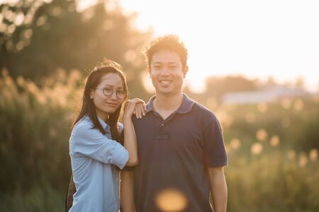 Young Asian couple in sunshine flare enjoying sunset relaxing having fun.