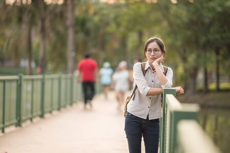 Young Asian woman with backpack  standing and looking for something in the park. Standard-Bild