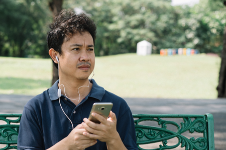 Asian man with smartphone sitting on the bench in the park Standard-Bild