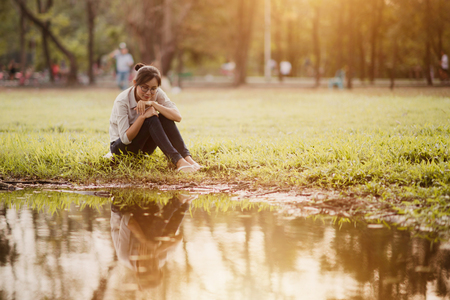 Asian woman sitting near swamp in the park.