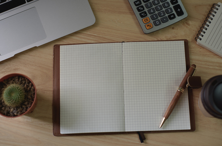 Top view of note book and pen with laptop on wood table. Standard-Bild - 96305433