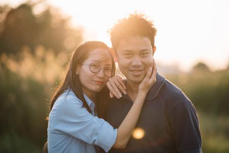 Young Asian couple in sunshine flare enjoying sunset relaxing having fun. Standard-Bild - 96305374