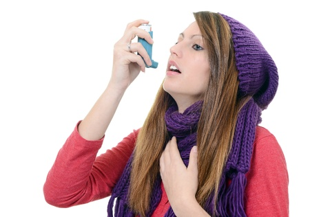 Woman with asthma using pump inhaler photo
