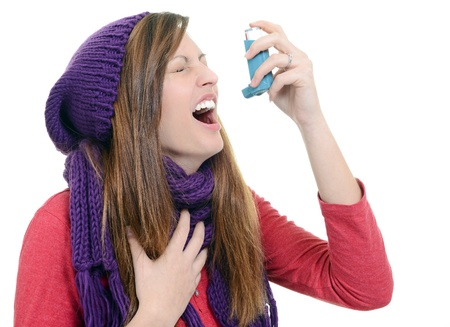 Woman with asthma using pump inhaler Stock Photo