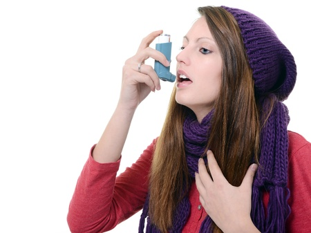 bronchial: Woman with asthma using pump inhaler Stock Photo