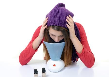 fumigador: Una mujer joven con los resfriados y la gripe inhalada aceites esenciales