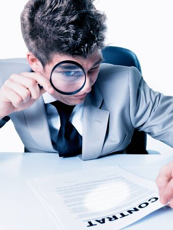 Homesome Businessman with magnifying glass reading the fineprint in a contract Stock Photo - 17796251