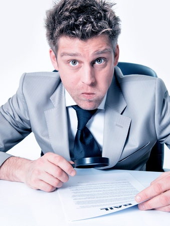 Expressive businessman with magnifying glass analyze contract photo