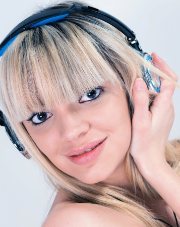 Portrait of Attractive girl listening to music with blue headphone photo