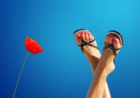 feet crossed: feet crossed and poppy symbolizing wellbeing