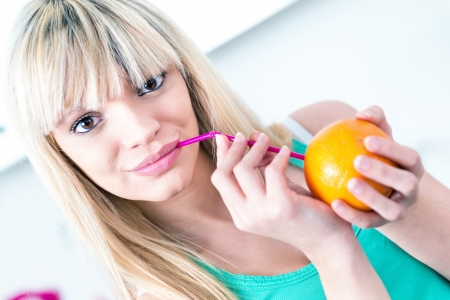 Cute girl drinking an orange from a straw Stock Photo - 17893458