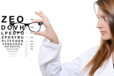 Woman with glasses and snellen eye chart in background photo