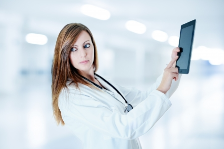 attractive doctor working with digital tablet at hospital photo