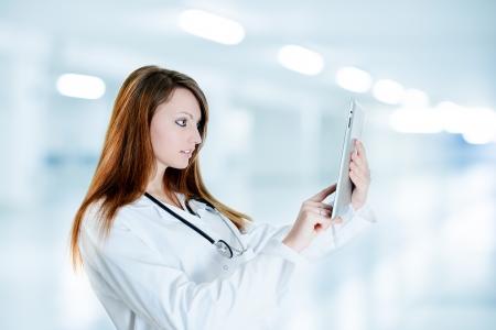 看護師を使用してデジタル タブレットと病院で実験用の上着を着ています。