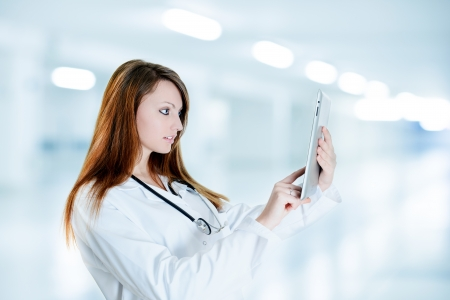 Nurse Using Digital Tablet and wearing a lab coat at hospital photo