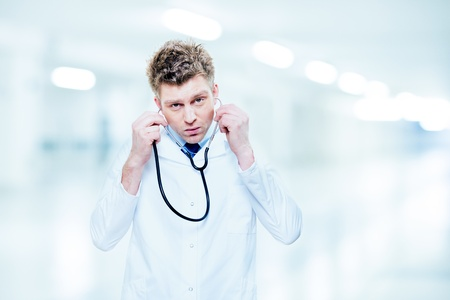 Handsome doctor listening with a stethoscope at hospital Stock Photo - 18125007