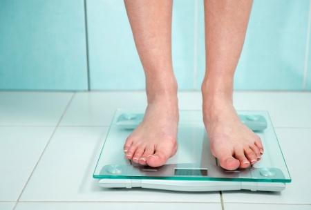 Primer plano de los pies de la mujer de peso en el baño Foto de archivo - 18435170