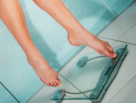 close-up of woman feet weighing in bathroom photo