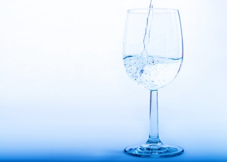 welling: Drinking water is poured from a bottle into a glass Stock Photo